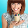 Attractive young woman holding box of crayons — Stock Photo