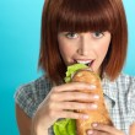 Beautiful young woman eating a big sandwich — Stock Photo #10114444
