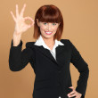 Attractive, young businesswoman showing ok sign — Stock Photo