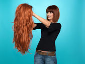 Pretty woman admiring long hair wig — Stock Photo