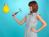 Pretty young woman breaking a light bulb — Stock Photo