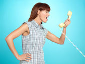 Attractive young woman screaming on the telephone — Stockfoto