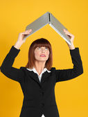 Attractive, young businesswoman holding laptop above head — Stock Photo