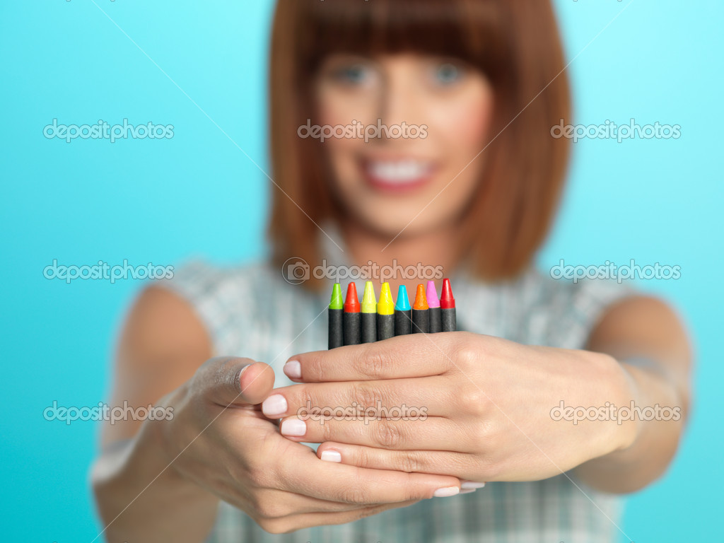 Beautiful young woman, holding a few color crayons, smiling, on blue background  Stock Photo #10114384