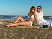 Young couple relaxing by the sea shore — Stock Photo