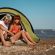 Happy young couple sitting in tent seaside — Stock Photo