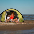Happy young couple sitting in tent seaside — Stock Photo #8342868