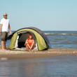 Happy young couple sitting in tent seaside — Stock Photo #8342878