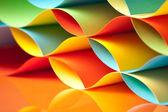 Gebogen, kleurrijke vellen papier met spiegel reflecties — Stockfoto