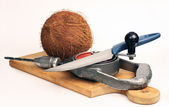 Coconut on a cutting board. A knife and a drill — Stock Photo