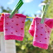 Pink baby sock hanging on the clothesline — Stock Photo