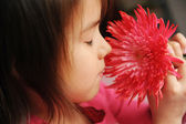 A girl smelling a flower — Stock Photo