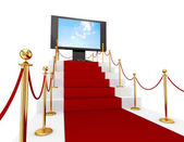 Red carpet on a stairs and LCD monitor. — Stock Photo