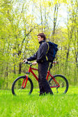 Man Cyclist with Bike and Backpack among the green nature — Stock Photo