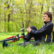 Happy Man Cyclist with Bike and Backpack sitting on green grass - Stock Photo