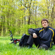 Happy mcyclist with bike and backpack sitting on green grass — Stock Photo #10478014