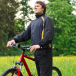 Stock Photo: Happy mcyclist with bike among green nature