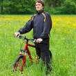 Man cyclist with bike among the green nature - Stock Photo