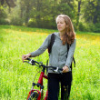 Happy womcyclist with bike among green nature — Stock Photo #10478151