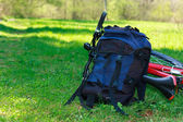 Backpack and Bike Lying on Green Grass — Stock Photo