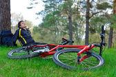 Röd cykel liggande på grönt gräs. cyklist slappnar i bakgrunden — Stockfoto