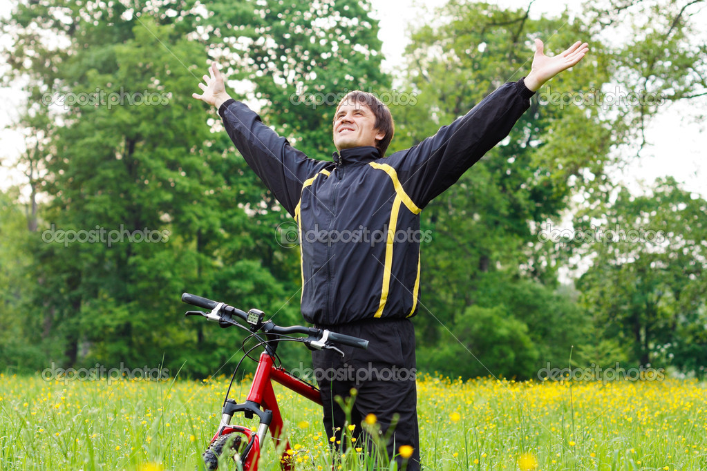 Excited happy man cyclist among the green blooming nature hands outstretched embracing vitality freedom. Outdoor — Stock Photo #10478127