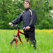 Man cyclist with bike among the green nature — Stock Photo