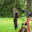 Royalty-Free Stock Photo: Woman cyclist with bike and backpack among the green nature