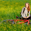Happy woman cyclist with bike among the blooming meadow — Stock Photo