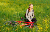 Woman cyclist with bike and backpack among the blooming meadow — Stock Photo