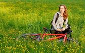 счастливая женщина велосипедиста с велосипеда среди цветущий луг — Стоковое фото