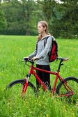 Cycliste femme avec vélo et sac à dos parmi la nature verte — Photo