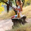 Young beautiful woman reading a book. Near it is the cat — Stock Photo