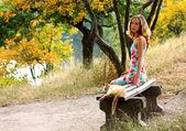 Genç güzel kadın ve bankta oturan kedi — Stok fotoğraf