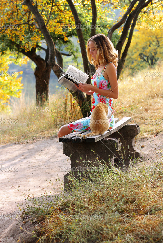 Young beautiful woman reading a book. Near it is the cat against a background of green sunlit nature — Stock Photo #8506109