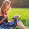 Beautiful woman sitting in the grass is reading book with apple in hand - Stock Photo