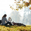 Womcyclist with read map sitting among green scenery — Stock Photo #8593477