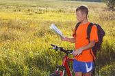 Cycliste homme lire que la carte est parmi le paysage vert — Photo