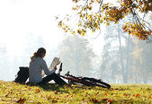 Woman cyclist with read the map sitting among the green scenery — Stock Photo
