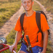 Stock Photo: Happy man cyclist sitting against a background of solar nature