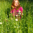 Beautiful woman among the grasses and chamomile — Stock Photo