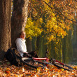 Womcyclist relaxing in autumn park — Stock Photo #8997419