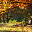 Woman cyclist relaxing in autumn park — Stock Photo