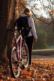 Vrouw fietser met fiets en rugzak in de herfst natuur — Stockfoto
