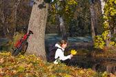 Kvinna cyklist avkopplande i höst park — Stockfoto