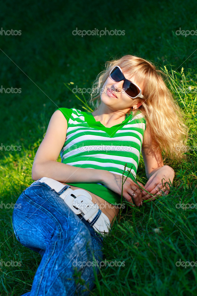 Beautiful happy woman in sunglasses illuminated by sunlight lie among the nature. Summertime outdoors — Stock Photo #8997378