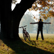 Excited woman cyclist standing in a park with hands outstretched — Stock Photo #9129163
