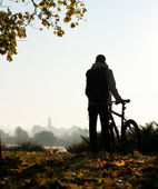 Silhouette of woman with bicycle by the break of day — Stock Photo