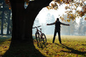 Excited woman cyclist standing in a park with hands outstretched — Stock Photo