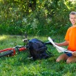 Smiling Man cyclist with map in hand sitting among the green nature — Stock Photo